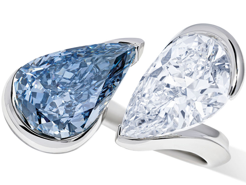 A twin stone ring featuring blue and white pear-cut diamonds