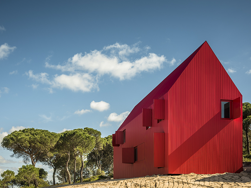 A red A-frame home framed by blue skies