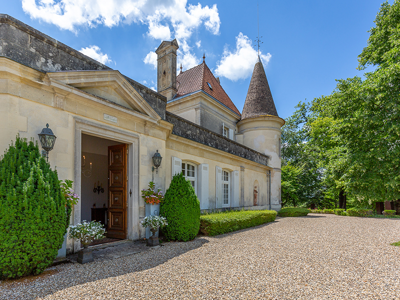 The front entrance of a grand limestone chateau