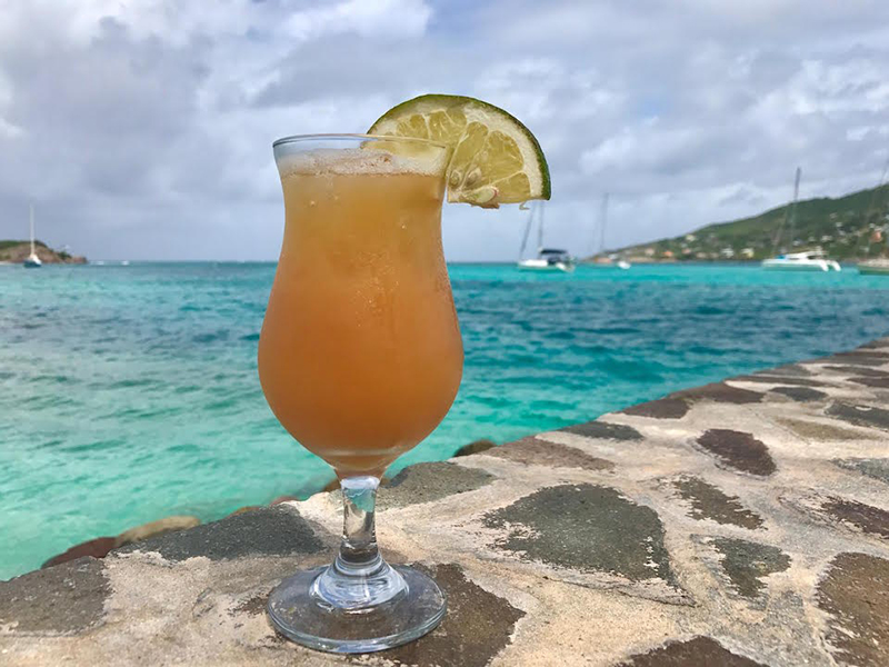 A rum punch cocktail next to a turquoise sea