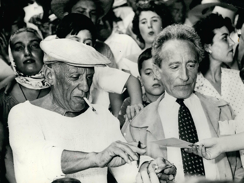 Pablo Picasso and artist Jean Cocteau signs autographs at a bull fight he organized in Vallauris, France