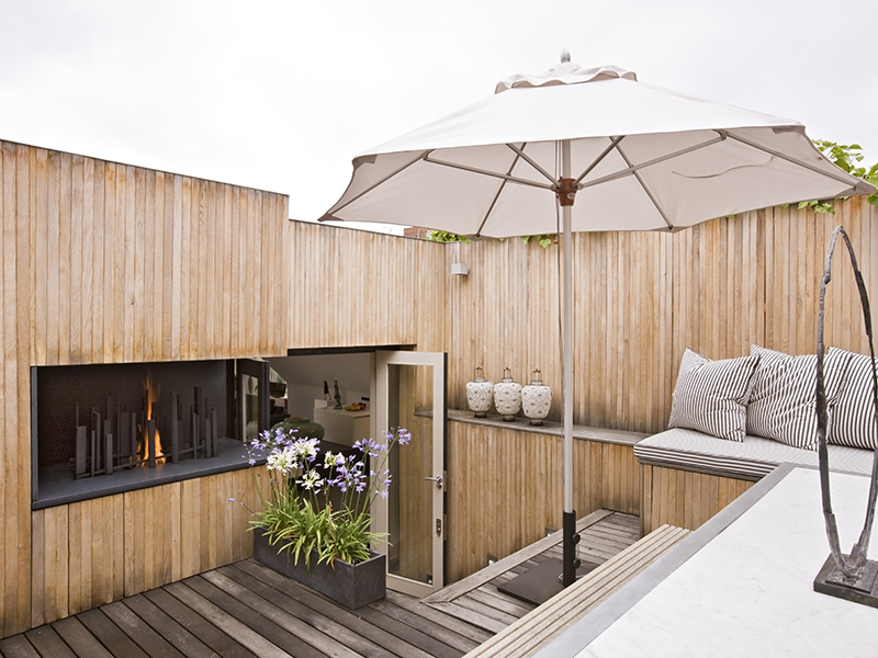 A wooden clad terrace with a built-in fireplace