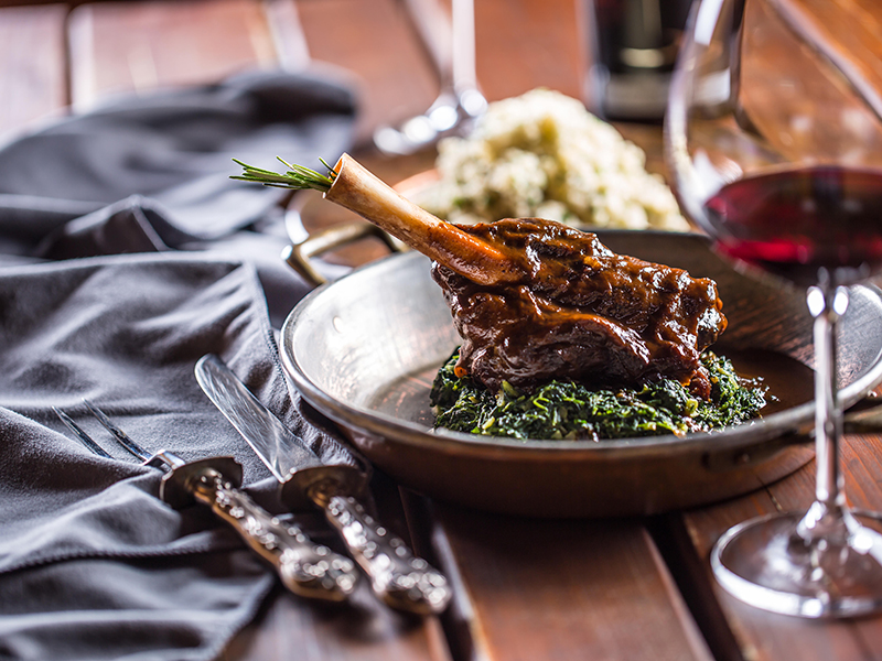 Roasted or confit Lamb Leg in pan with spinach and red wine.