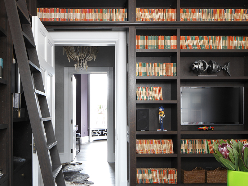 A home library showcasing many books with orange spines