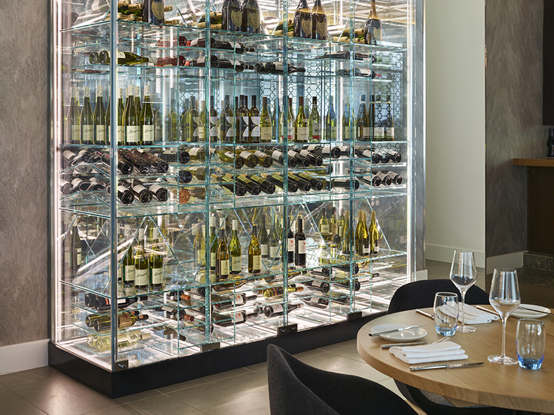 A well-lit wine aquarium within a dining room