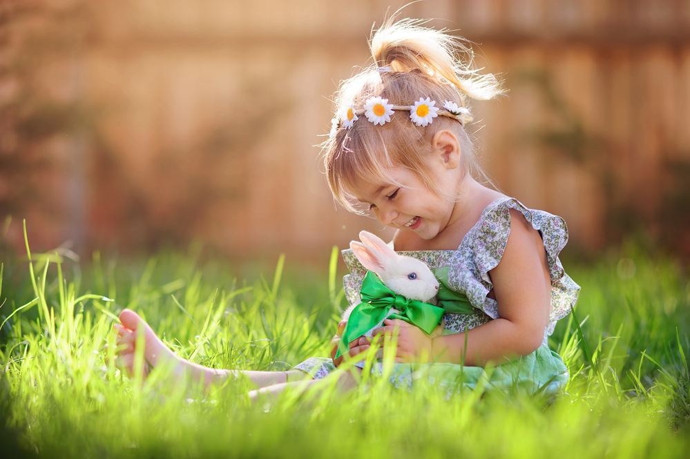 Cute little girl with a bunny rabbit at easter with green grass