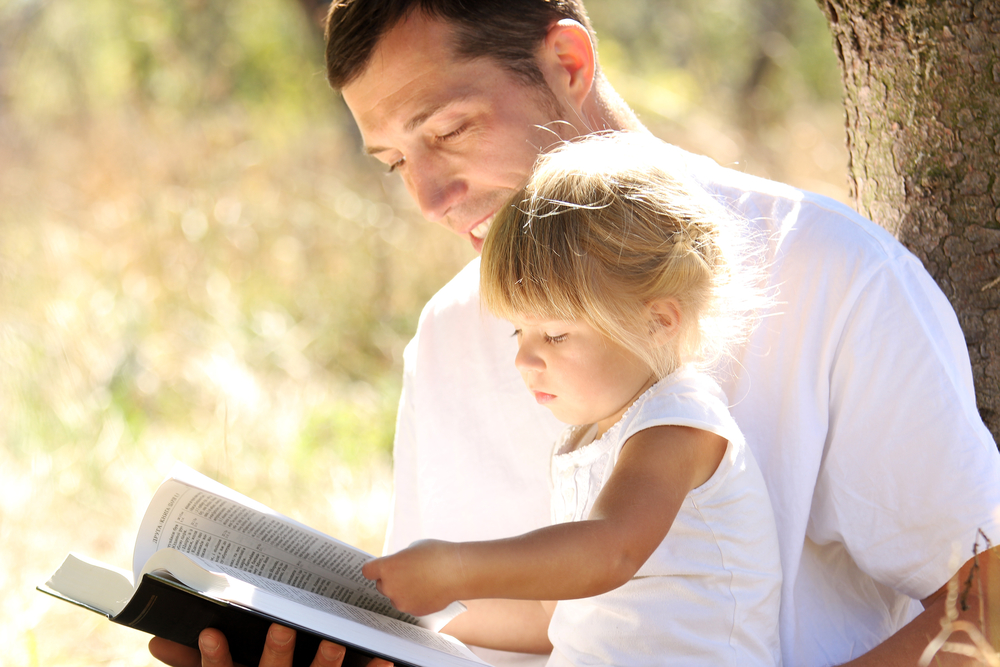 Dad reads Bible with daughter