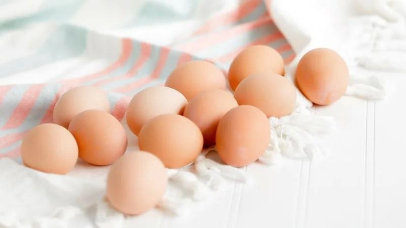 a dozen Organic, Pasture Raised Eggs on a dish towel