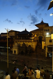 A traditional Nepali temple lit up orange under a deep blue sky at dusk