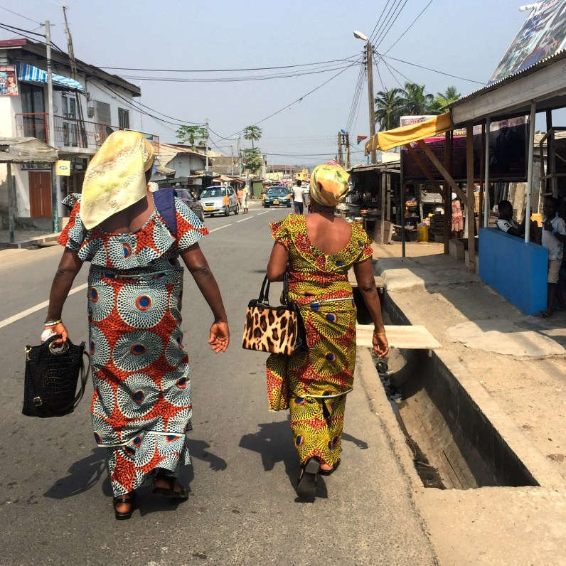 Two women walking away from the viewer on a street wearing the traditional Ghanaian outfit of a kaba and slit in African print.