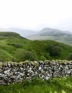 An old stone wall with foggy mountains in the background on the West Highland Way