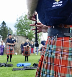 A close up of a person's hands playing a bagpipe and the tartan of their kilt with other bagpipers blurred in the background