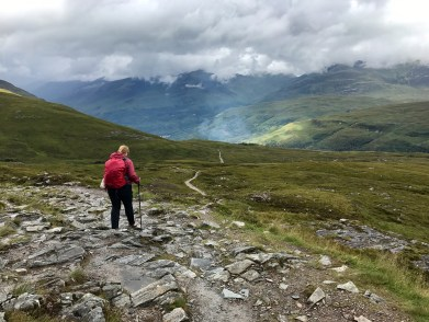 A woman stands on a rocky path in front of mountains with a red backpack on the West Highland Way