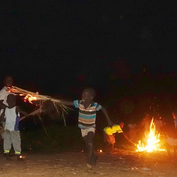 a small boy, holding a bundle of grass that is lit on fire runs towards the camera and a fire burns in the background under a black sky