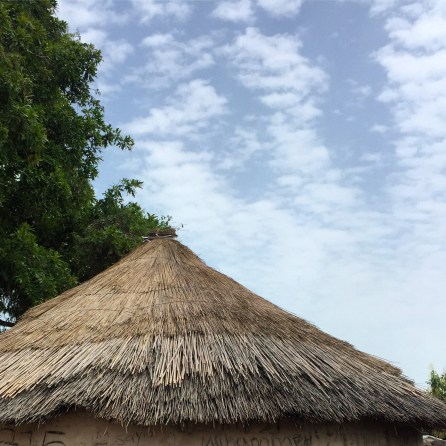 a thatched roof of a round mud hut against a hazy blue sky with scattered white clouds