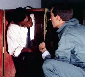 "Barney (Greg Morris) and Rollin (Martin Landau) check themselves into the baggage compartment in ""The Astrologer"""