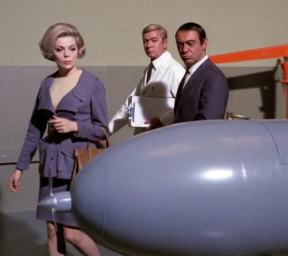 "Cinnamon (Barbara Bain) inspects a warhead in ""Doomsday"" (accompanied by villains Wesley Lau and Arthur Batanides)"