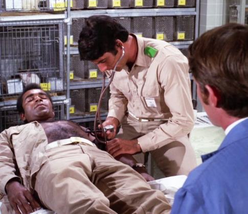 Barney (Greg Morris) is tended by Doug (Sam Elliott) while reluctant IMF accomplice Jerry Carlin (Christopher Connelly) looks on