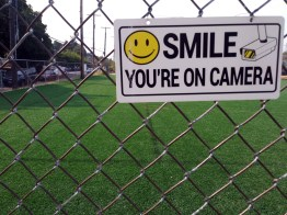A turf field stands behind a fence and a warning that unintended uses of the space will be caught on camera.