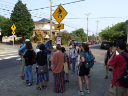 Field trip participants gather around Charlie as he discusses the African American history of the neighborhood.