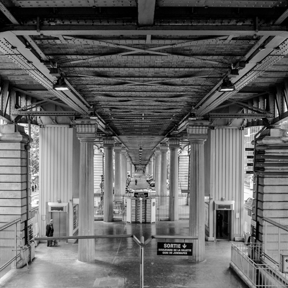 Black and white image of a metro station in Paris, France.