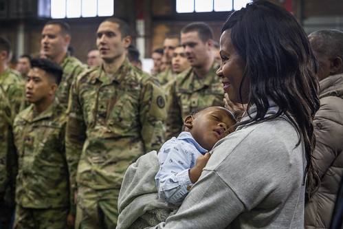 A family member listens as Soldiers with Headquarters and Headquarters Troop, and Alpha and Bravo Troops, 1st Squadron, 102nd Cavalry, New Jersey Army National Guard, sing the Army Song after the farewell ceremony at the armory in Westfield, N.J., Jan. 21, 2019. The three units are deploying to the Hashemite Kingdom of Jordan in support of Operation Spartan Shield. (New Jersey National Guard photo by Mark C. Olsen)
