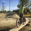 Riding around the perimeter of the pumptrack on the logs used to create a division between the commuter path and the pumptrack.
