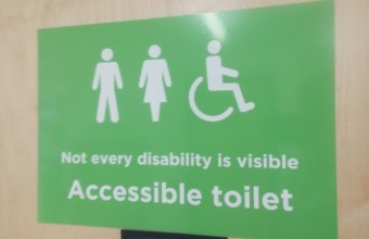 "Image of two people standing and one in a wheelchair with the caption ""Not all disability is visible"" accessible toilet."