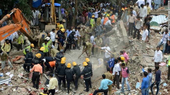 Rescue workers look for survivors in debris at the site of a building collapse in Mumbai