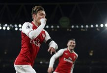 Mesut Ozil celebrates scoring the fourth goal against Huddersfield