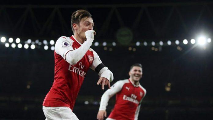 Mesut Ozil celebrates scoring the fourth goal against Huddersfield