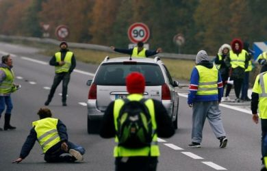 A driver forces a car through a group of protesters in Donges, western France