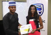Usman Imanah, Marketing and Communications Manager at StanbicIBTC presenting a Certificate of Participation to a journalist