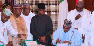 Vice President Osinbajo, lawmakers and other cabinet members look on as President Muhammadu Buhari signs 2019 budget