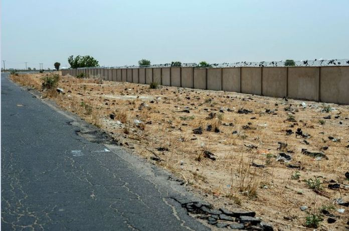 Nigeria's military built this barrier to wall off what had been farmland on the northern edge of the base in Maiduguri. An expanding cemetery lies on the other side.