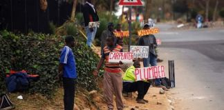 South Africans looking for jobs advertise on the road