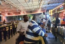 Segun Adebutu meeting with business partners at a lounge