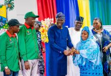 Lagos State Governor, Mr. Babajide Sanwo-Olu (middle) presenting keys to an allottee, Mrs. Fatima Kosoko