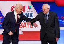 Joe Biden and Bernie Sanders do the elbow bump before the Democratic debate