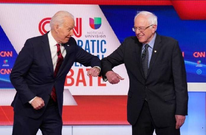 Joe Biden and Bernie Sanders do the elbow bump before the Democratic debate