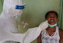 A woman opens her mouth for the heath worker to collect a sample for coronavirus testing