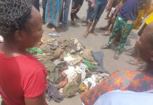 Residents gather around the drainage where the supposed madmen and suspected kidnappers reside in Shogunle, Oshodi