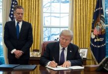 President Donald Trump signs a document in the Oval Office