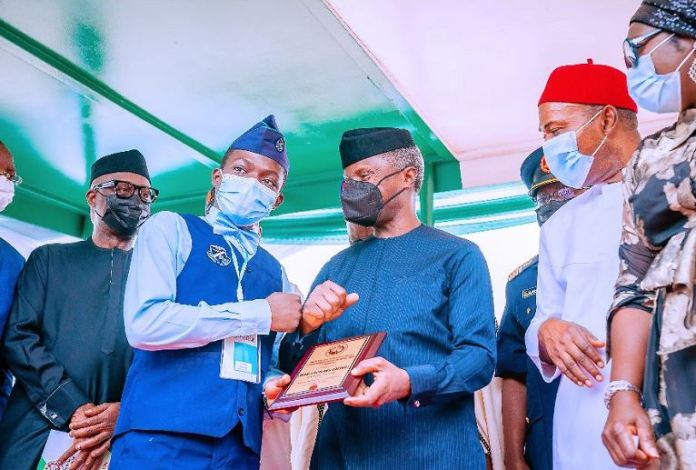 Vice President Yemi Osinbajo presents the First Place Prize to the winner of the 774 Young Nigerian Scientists Presidential Award Edeani Godswill at the 2021 Tech & Innovation Expo Research