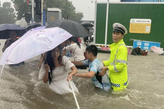 Police officer guides residents to cross a flooded road during the heavy rainfall in China