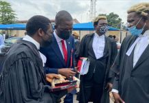 EFCC chairman, Abdulrasheed Bawa consulting with lawyers at the trial of Abubakar Ali Peters and his company, Nadabo Energy Limited in Lagos State