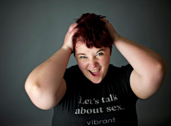 """[pic of Kirsten, hands on her head as thought she wants to pull out her hair; she is somewhere between screaming and laughing, and only visible from the chest up; she has on black jeans, a gray tee shirt with white text """"Let's talk about sex - Vibrant""""; her hair is reddish-purpleish]"""