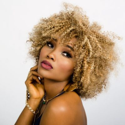 An African American woman from the shoulders up; she is posing for a photo shoot; she has blonde hair in tight ringlets and is wearing jewelery