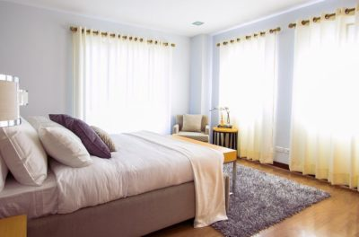 A bed with pillows sits in a soothing room; there is a hardwood floor with a rug at the end of the bed; light is coming through the sheer white curtains
