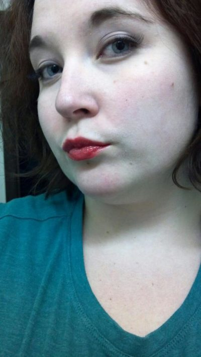 A white girl (me!) with a teal shirt; subtle makeup save for red lips and eyeliner